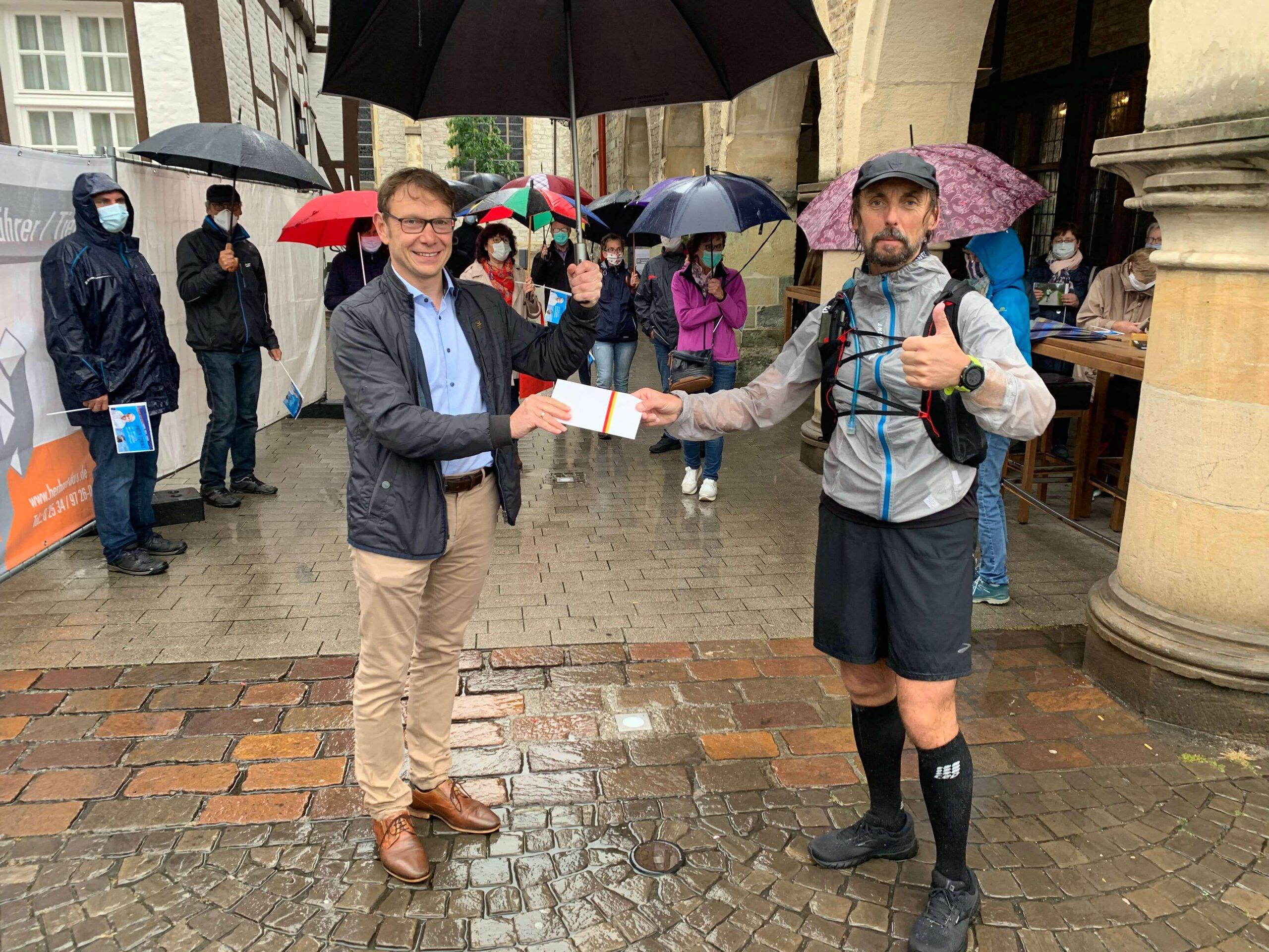 Bürgermeister Lothar Christ überreichte Pater Tobias bei seinem Zwischenstopp vor dem Rathaus eine Spende in Höhe von 111 Euro. Foto: Viefhues