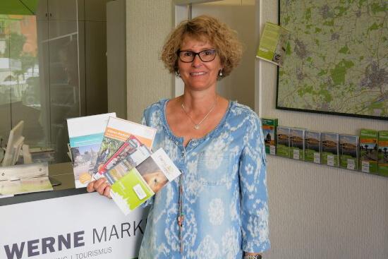 Andrea Nienhaus zeigt das buchstäblich breit gefächerte Angebot an Karten vor. Sie und ihre Kolleginnen helfen gern bei der Auswahl von einer Ein- oder Mehrtagestour. Foto: Gaby Brüggemann