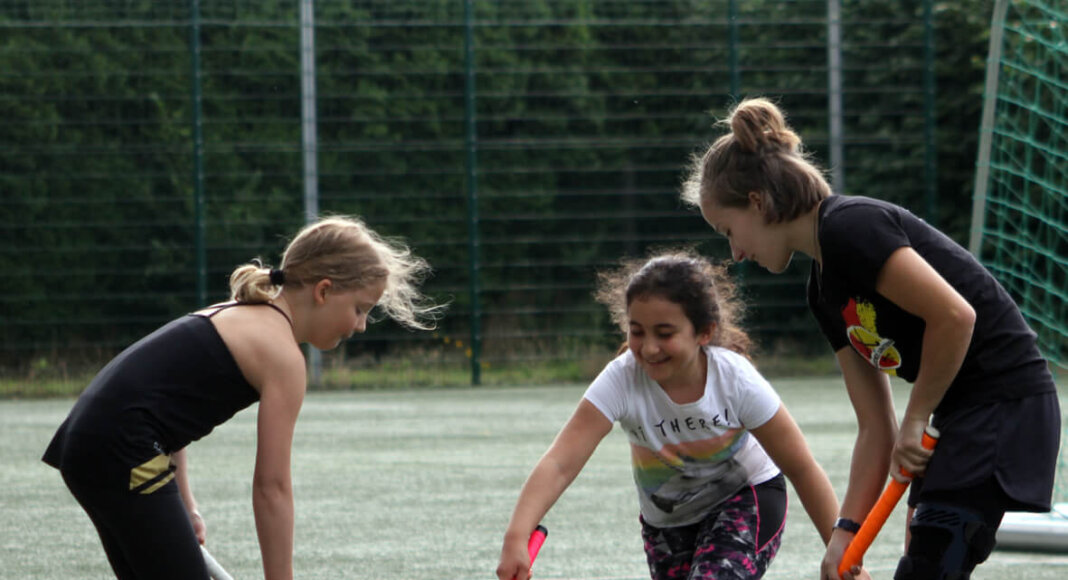 United-Trainerin Jojo Schmitz erklärt zwei Mädchen die Technik im Hockeysport. Foto: Wagner