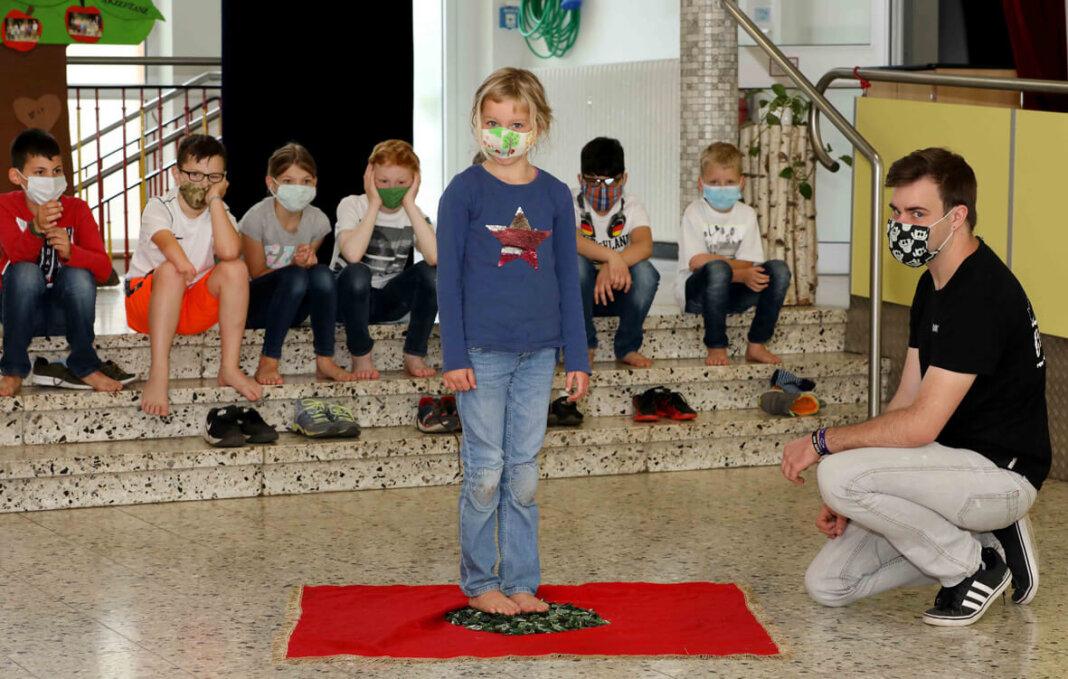 Ganz schön mutig! Die Kinder an der Kardinal-von-Galen-Schule haben schon gelernt, wie es sich anfühlt, wenn man über Scherben läuft. Foto: Christoph Volkmer