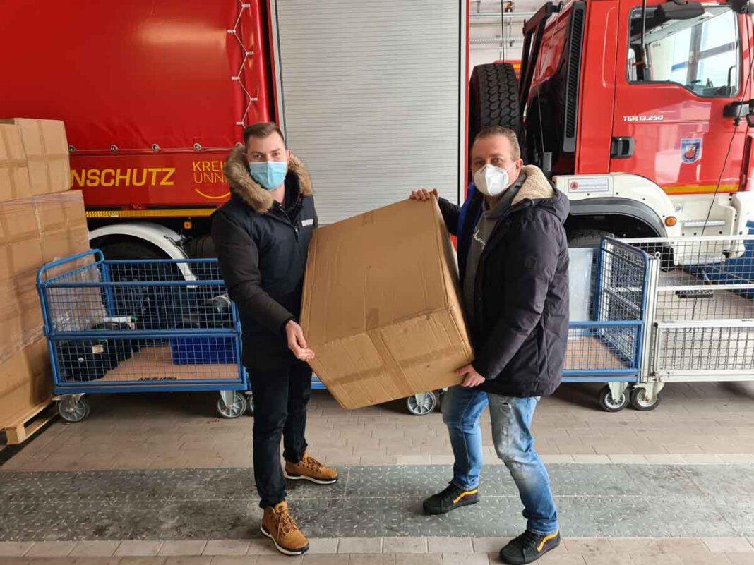 Rudolf Meisner, im Auftrag des Ordnungsamts der Stadt Werne, und Kai Proske vom Bevölkerungsschutz des Kreises beim Verladen der Masken für die Stadt Werne. Foto: Patrick Isken