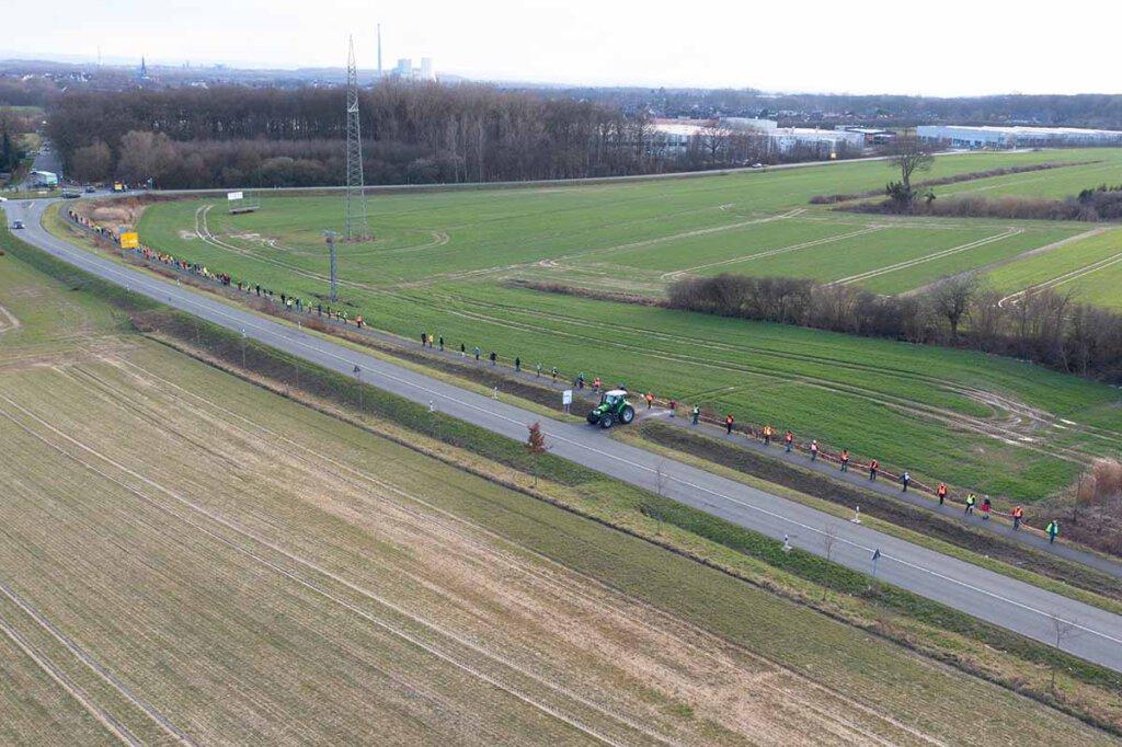 Links auf dem Foto ist ein Ausschnitt des Gebietes, das für ein neues Gewerbegebiet herhalten soll. Die Menschenkette demonstrierte die Länge der westlichen Ausdehnung. Foto: Kreativshooting/T. Schütte