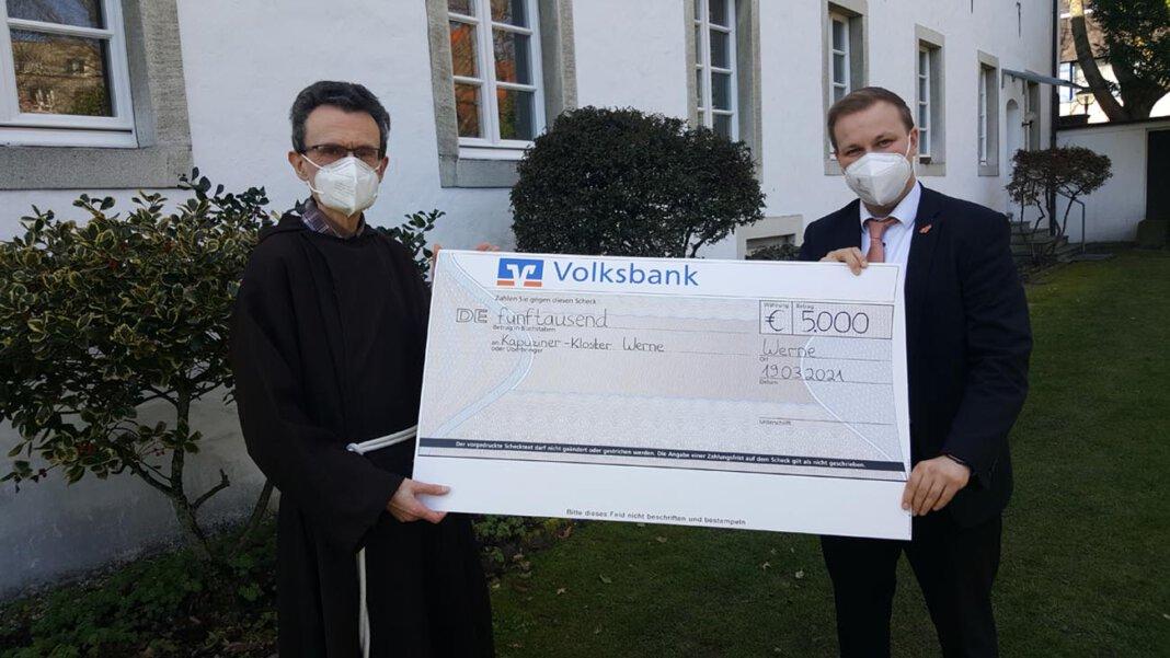 Pater Romuald nahm den Spendenscheck aus den Händen von Volksbank-Sprecher Philipp Gärtner entgegen. Foto: Wagner