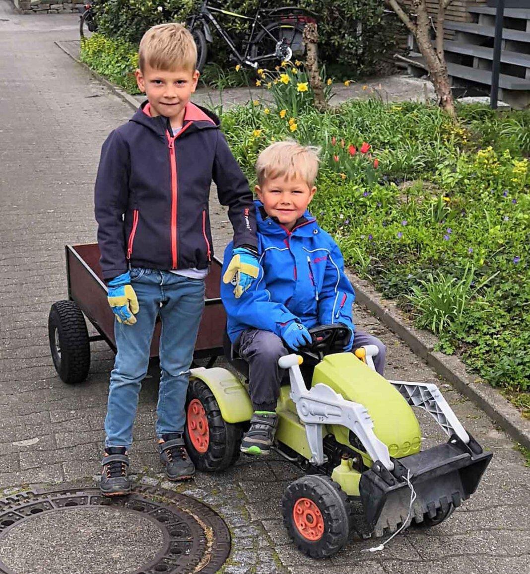 """Unterwegs mit Tret-Trecker und Anhänger: Elias Brinker (5) und Enno Hagenkamp (6) reinigen ihr """"Revier"""" von Müll. Foto: Isabel Schütte"""
