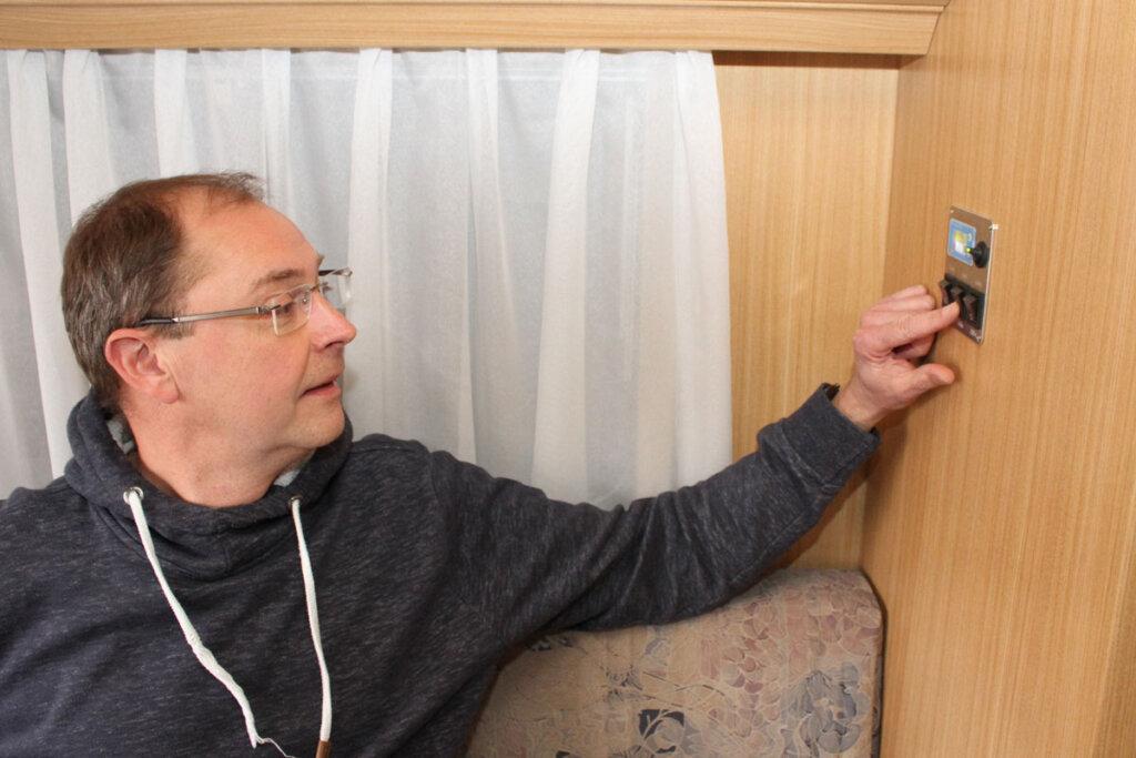 Mit einem kleinen Regler kann Heiko Mönster die Energieversorgung im Wohnwagen regeln und kontrollieren. Gleiches geht auch mit der dazugehörigen App auf seinem Handy. Foto: Isabel Schütte