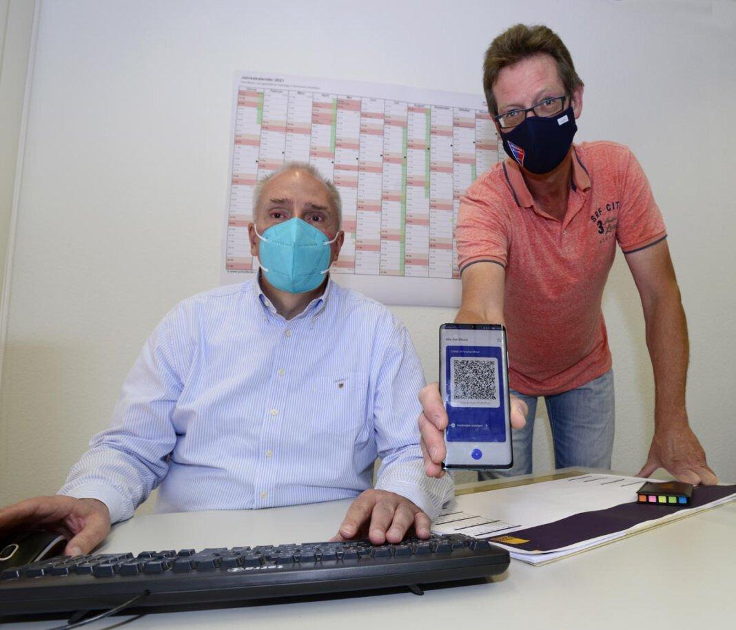 Am Mittwoch, 30. Juni, digitalisiert der Werner Apotheker Udo Lucas (l.) in der Geschäftsstelle des Werner SC Corona-Impfzertifikate. WSC-Vereinsvorsitzender Oliver Grewe hat den QR-Code bereits im Handy gespeichert. Foto: Stengl