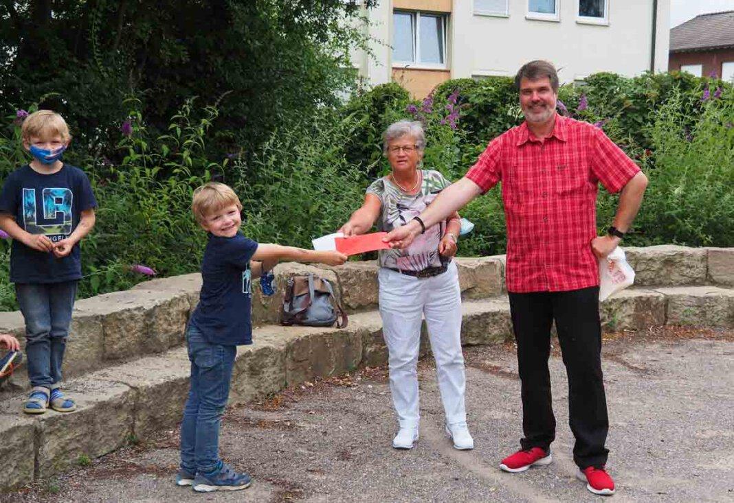Marita Funhoff und Michael Thews (SPD) förderten das Ferienprogramm an den drei Werner Grundschulen mit einer Spende. Auf dem Foto überraschen sie OGS-Kinder an der Wiehagenschule. Foto: SPD