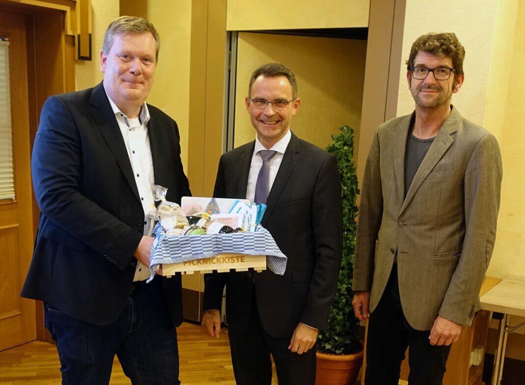 Bürgermeister Thomas Stohldreier (l.) und Geschäftsführer Martin Bußkamp (r.) bedankten sich gestern Abend beim bisherigen Vorsitzenden Dr. Bert Risthaus für über elf Jahre Engagement mit einer Picknickkiste und einem Ascheberg-Liegestuhl. Foto: Ascheberg Marketing e.V.