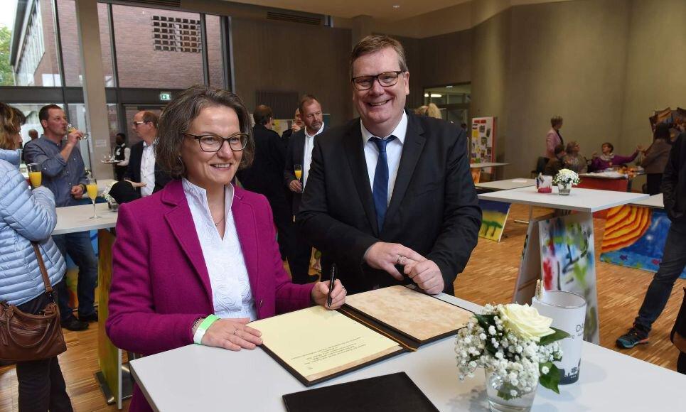 Ministerin Ina Scharrenbach trägt sich ins Goldene Buch, Bürgermeister Thomas Stohldreier freut´s.